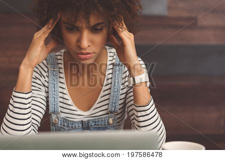 It hurts. Gloomy young woman is sitting at table in vegetarian cafe and touching her temples while having headache and expressing suffering. Wooden wall on background