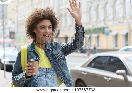 Hi. Cheerful mulatto woman is waving hello and expressing gladness while standing outdoors with cup of coffee