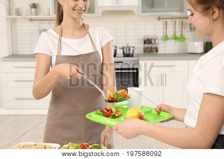 Young woman serving lunch to school girl at canteen