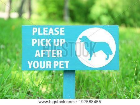 Signboard with text PLEASE PICK UP AFTER YOUR PET at park
