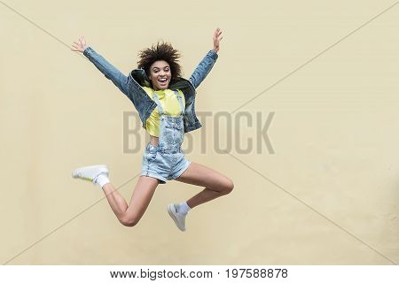 Back to childhood. Playful hipster girl is jumping outdoors against wall while expressing happiness. She is looking at camera with smile. Copy space in the right side