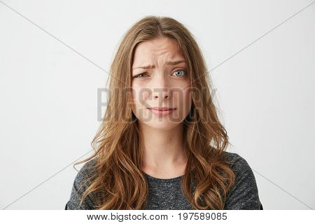 Portrait of young pretty girl looking at camera with contempt over white background. Copy space.