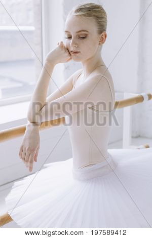 Elegant ballerina standing near the window and hunging her arms over the stand. Girl is dreaming about being a famous dancer having big perfomances. She is relaxed and calm. Close up