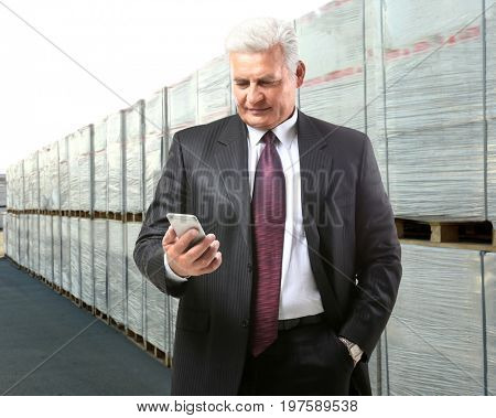 Mature manager using smartphone near goods, outdoors. Wholesale and logistic concept