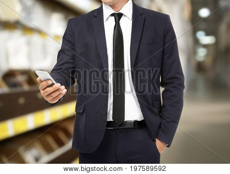 Manager using smartphone at storehouse. Wholesale and logistic concept