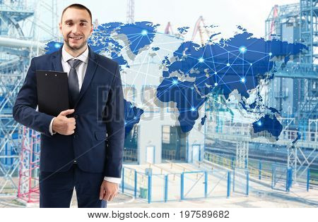 Manager with clipboard and factory on background. Wholesale and logistic concept