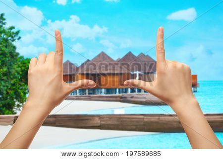 Woman making photo frame with hands and bungalows on background