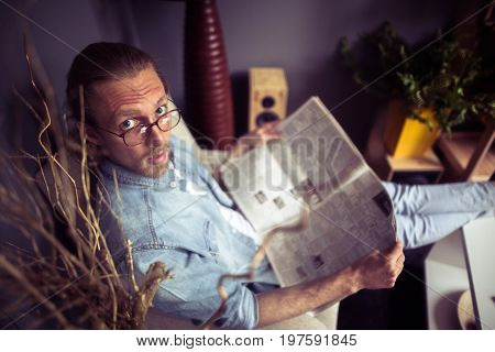 Top view of man sitting in chair with newspaper. Male holding newspaper in his hands. Toned image.