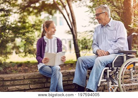 Disabled grandfather in park spending time together with his granddaughter reading book outdoor