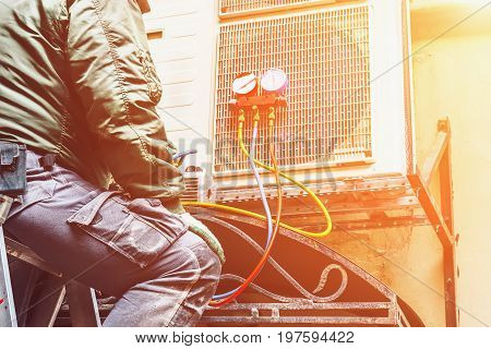 The worker repairs or prevents the air conditioner on the wall, Air Conditioning Repair concept, toned