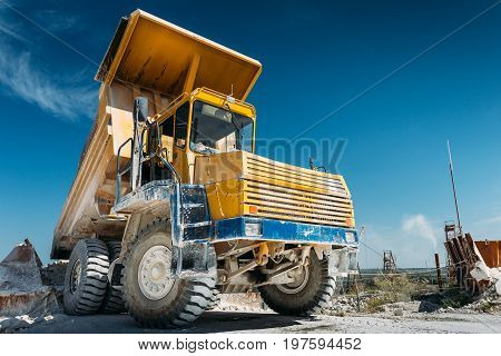 Big yellow mining truck vehicle, truck unloads mined ore or chalk or limestone. Mining industry concept with copy space