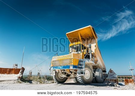 Big yellow mining truck. Work industrial machinery, processes of extraction of limestone mining
