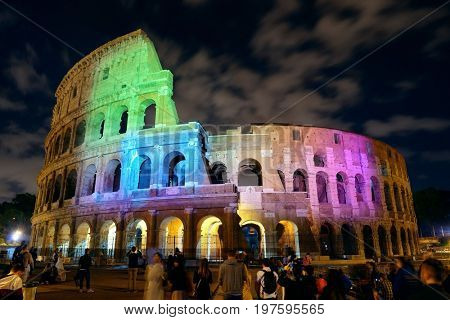 Colosseum at night with tourists and colorful lights, the world known landmark and the symbol of Rome, Italy.