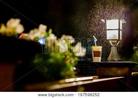 A paper glass in a coffee shop at night with the light of a lantern