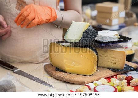 Gastronomic products for gourmets, traditional italian cut cheese heads on the market counter, woman hands of the seller with a knife