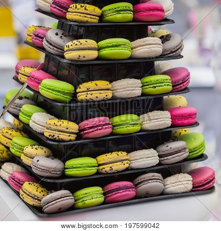 Pyramid of different french colorful macaroons various flavors and diffrent colors, french sweet cookies from almond flour, on the market counter