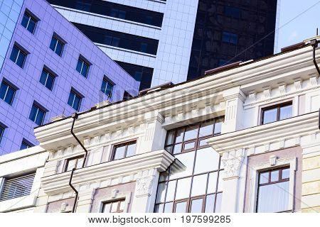 An Ancient Building Next To A Modern Office Building. Abstract Image Of Modern And Historical Forms