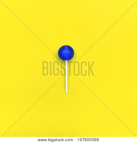 Lollipop Flat lay Minimal concept Blue round lollipop is lying on a yellow background Trendy bright photo in modern pop art style Top view