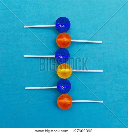 Lollipop Flat lay Minimal concept Six multicolored round lollipops are lying in a row on a light blue background Trendy bright photo in modern pop art style Top view