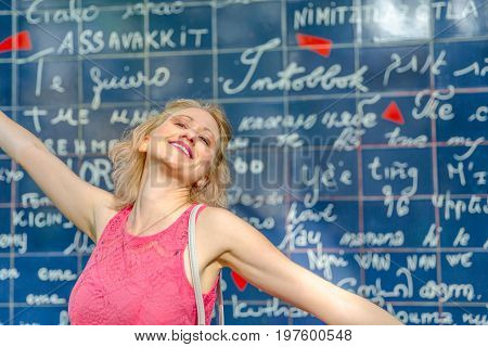 Smiling elegant woman with open arms enjoying in front of the popular Mur des Je t'aime. I Love You Wall is a monument in Jehan Rictus garden square near Place des Abesses, in Montmartre Paris, France