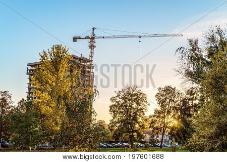 Urban housing construction. Tower crane with a multi-storey building under construction in the evening among autumn trees. Wide angle.