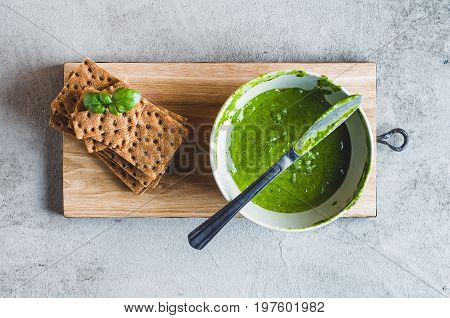 Crispbread And Green Salsa On A Grey Concrete Background