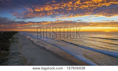 Aerial view of colourful sunrise through a cloudy sky, on Gold Coast beach.