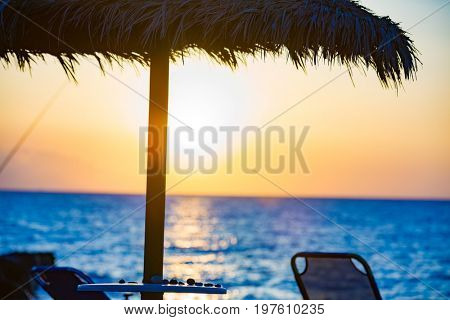 Beach umbrella and sun beds on the sea beach at sunset
