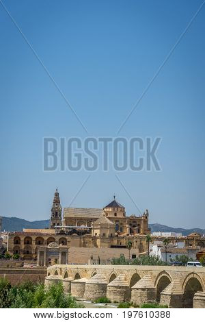 The Roman Bridge, Bell Tower And The Mosque Church Of Cordoba Across The Guadalquivir River, Spain,