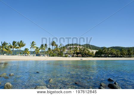 Tranquil view of Airlie Beach Queensland Australia across a rocky shoreline and calm ocean to the tropical beach with palm trees and resort buildings