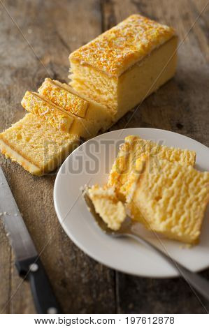 Slices of a fresh cake with lemon icing served on a side plate with a fork viewed high angle on a rustic wooden table