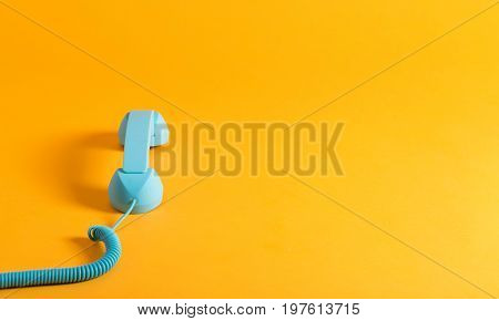 Vintage style blue telephone handset on a yellow background