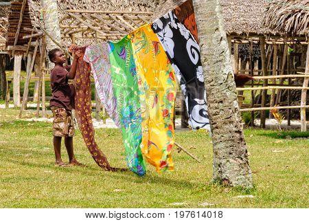 A local vendor with colourful sarongs fluttering in the breeze at Champagne Beach - Espiritu Santo, Vanuatu, 26 September 2012