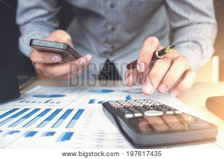 Business man or accountant working Financial investment on calculator with calculate Analyze business and market growth on financial document data graph and smart phoneAccountingEconomiccommercial.