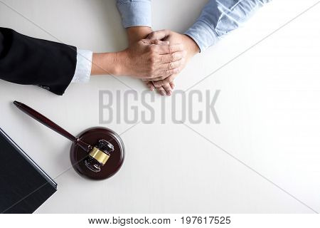 Image of Male lawyer or judge help encourage client customer working with gavel and Law book report the case on table in modern office Law and justice concept.