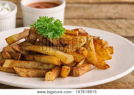 Homemade french fries serve with ketchup and sour cream or mayonnaise. Golden brown crispy french fries sprinkle with salt and oregano on white plate for snack or appetizer.Delicious french fries served on wood table with dipping sauce.