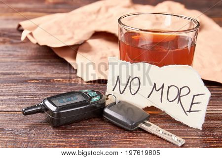Booze in glass, car keys, paper message. Message no more, alcohol in glass, car keys on wooden background. Automobile accidents and abuse of alcohol.