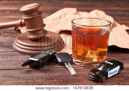 Booze driving concept. Gavel, driving keys, whiskey, police, wooden background. Hard penalty of drunk driver.