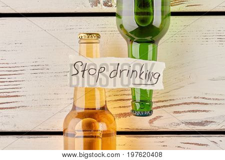 Stop drinking and start feel life. Message on bottles, vintage wooden table.