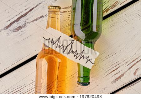 Alcohol hard affects health. Bottles with alcohol, cardiac impulses image, old boards. Heart problems with alcohol.
