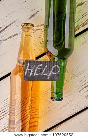 Help to defeat the alcoholism. Bottles, message, old floor. Need of professional support.