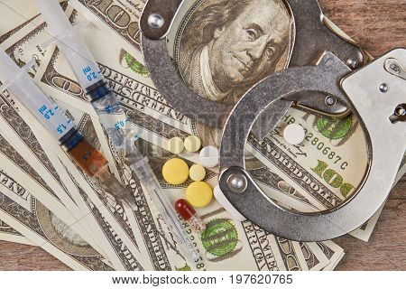 Illegal drugs trafficking, law punishment. Syringe with narcotic substance, pills, money, handcuffs close up.
