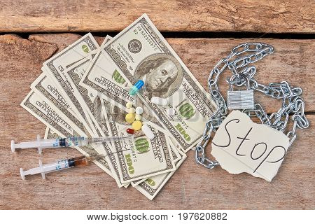 Syringes, money, pills, chain, message. Narcotics and dollars, message and chain with padlock, old wooden background.