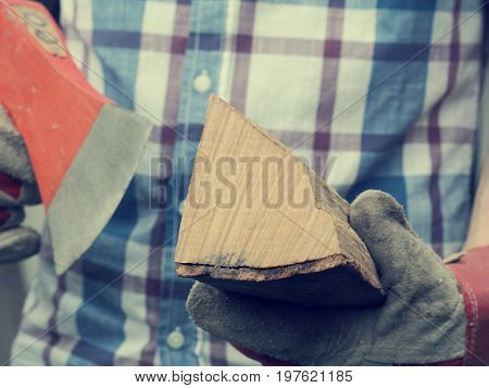 Young man holding an axe and fire wood selective focus on wood retro film stylized alternative energy concept