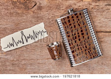 Pocket container for alcohol. Hip flask for whiskey, paper image of cardiac impulses. Alcoholic beverages harmful for health.