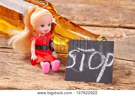 Stop drinking alcohol concept. Bottle of lager near little toy doll, message stop, old wooden background. Metaphor concept stop drink alcoholic beverages.