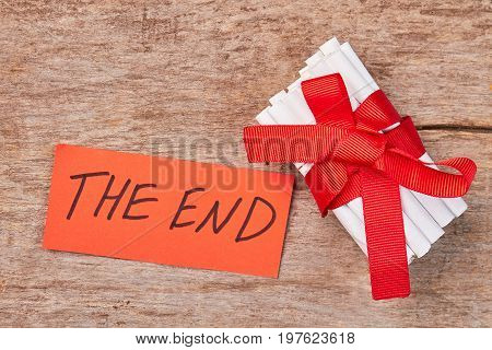 Message the end, tobacco cigarettes. Pile of white toxic cigarettes with red bow and ribbon, wooden background.
