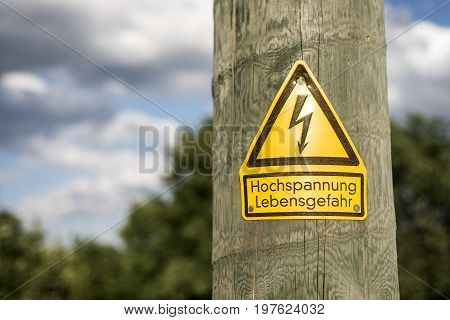 German high voltage sign mounted on wooden pole with green tree in the background