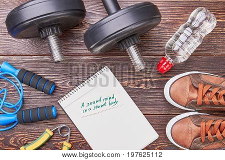 Sound mind in sound body. Paper notebook, jumping rope, dumbbells, water, sport shoes, wooden background.