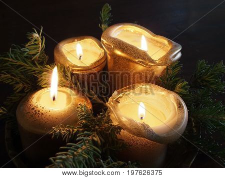 Four golden candles and pine tree branches forming a Christmas decoration on a table Melbourne 2016